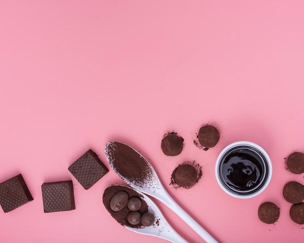 Plat lag mix van chocoladesnoepjes op roze achtergrond met kopie ruimte