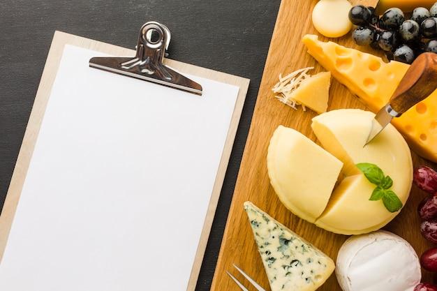 Plat lag mix van gastronomische kaas en druiven op snijplank met lege laptop