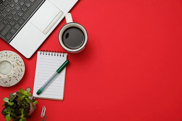 Plat lag moderne werkruimte rood bureau met laptop, bril, smartphone, koffiekopje.