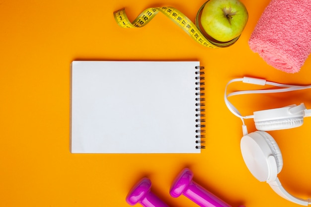 Plat lag notebook en appel op gele achtergrond