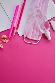 Plat lag onderwijs na de coronavirus-pandemie, terug naar school in een nieuwe realiteit, schoolbenodigdheden, beschermend masker en antisepticum op een roze achtergrond, ruimte voor tekst