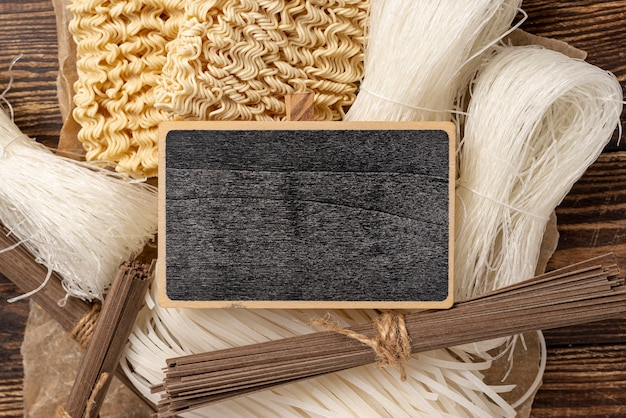 Plat lag ongekookt assortiment van noedels op houten achtergrond met leeg bord