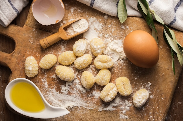 Plat lag ongekookte aardappel gnocchi op snijplank met eieren