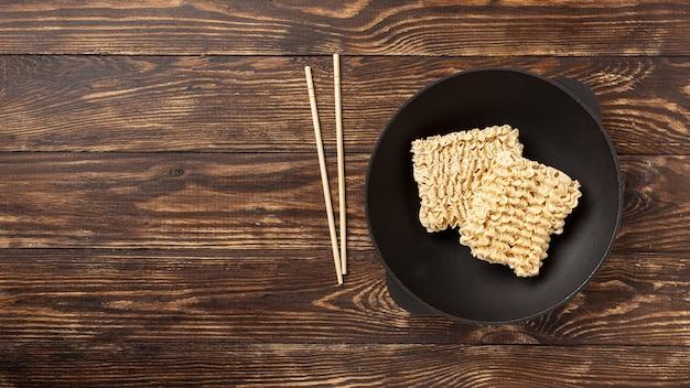 Plat lag ongekookte noedels op plaat en eetstokjes met kopie ruimte