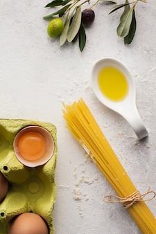Plat lag ongekookte spaghetti olijfolie en eieren