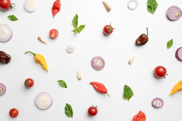 Plat lag ontwerp van groente, kruiden en specerijen op witte achtergrond.