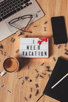 Plat lag op een houten tafel een lichtbak met het opschrift ik heb een vakantie nodig een vliegtuig symbool een laptop...