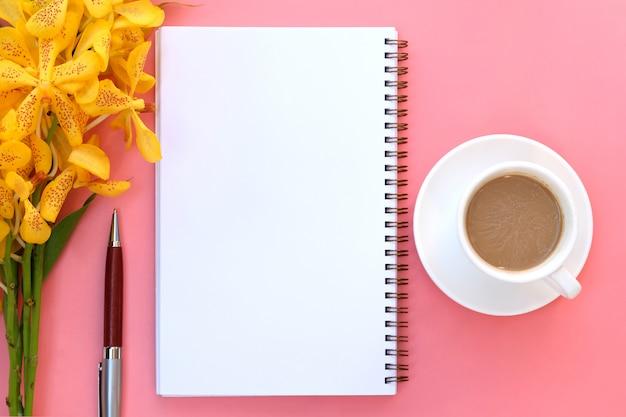 Plat lag open notebookpapier en een kopje koffie op roze.