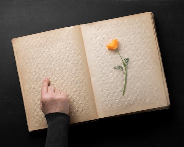 Plat lag oud brailleboek met bloem