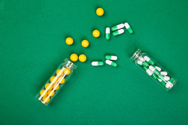Plat lag overhead van gele en groene pillen in glazen pot op papier achtergrond