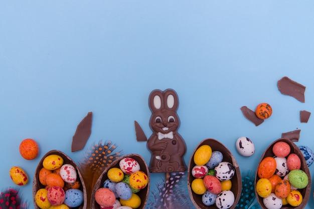 Plat lag paaseieren jagen snoep concept met chocolade konijn en eieren op blauwe achtergrond kopie ruimte