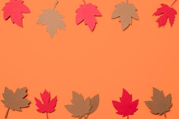 Plat lag papier herfstbladeren op oranje achtergrond met kopie ruimte