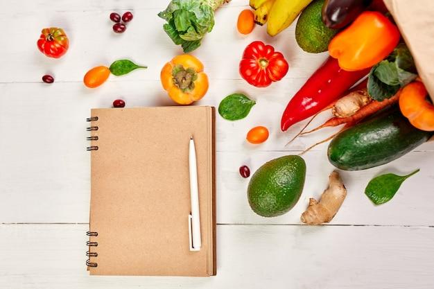 Plat lag papieren boodschappentas met assortiment van verse groenten en fruit