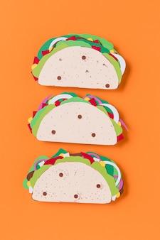 Plat lag papieren taco's op een oranje achtergrond