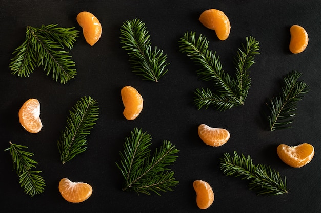 Plat lag patroon van sinaasappel mandarijn plakjes en kleine dennentakken