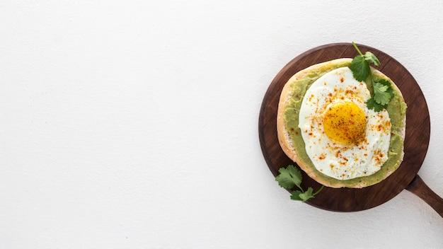 Plat lag pitabroodje met avocadopasta en gebakken ei met kopie-ruimte op snijplank