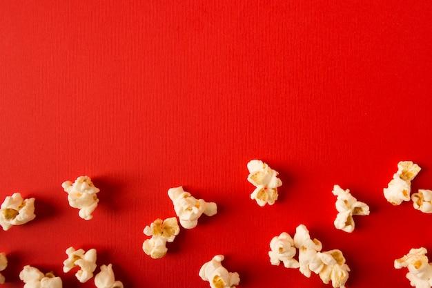 Plat lag popcorn assortiment op rode achtergrond met kopie ruimte
