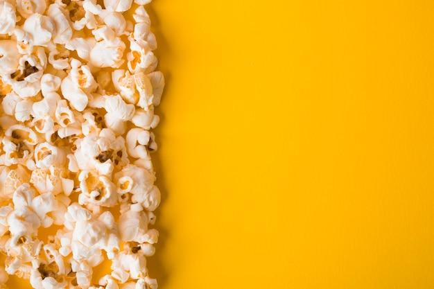 Plat lag popcorn op gele achtergrond met kopie ruimte