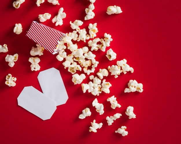 Plat lag popcorn op rode achtergrond en lege bioscoopkaartjes