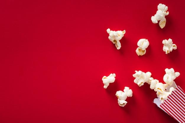 Plat lag popcorn op rode achtergrond met kopie ruimte