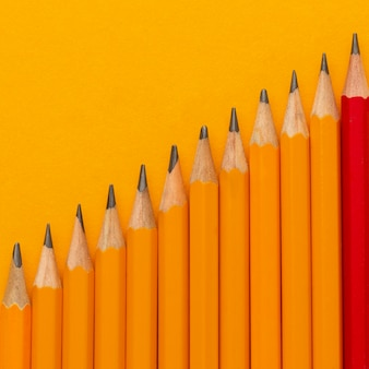Plat lag potloden op oranje achtergrond