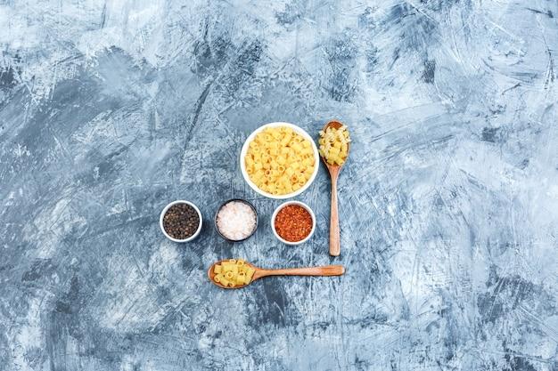 Plat lag rauwe pasta in kom en houten lepels met kruiden op grungy gips achtergrond. horizontaal