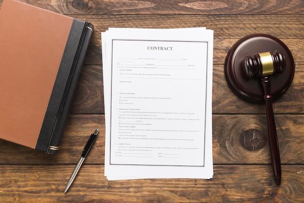 Plat lag rechter hamer en boek met contract