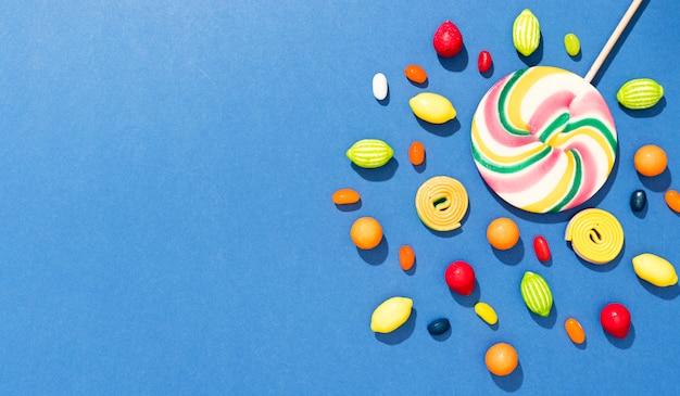 Plat lag regeling van snoepjes op blauwe achtergrond met kopie ruimte
