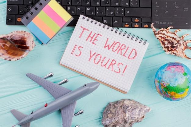 Plat lag reiziger accessoires op hout achtergrond met kladblok. de schelpen van de vliegtuigbol op blauw bureau.