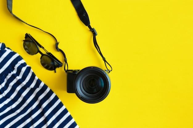 Plat lag reizigerstoebehoren op gele achtergrond met blauwe kleding, camera en zonnebril.