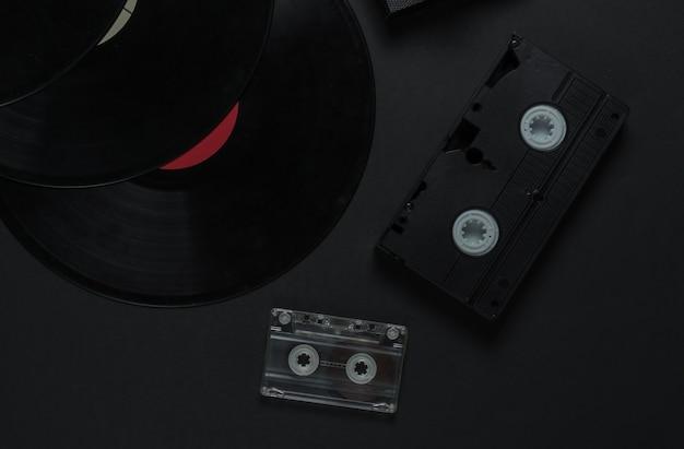 Plat lag retro media en entertainment. vinylplaat, audiocassette, vhs op zwarte achtergrond. jaren 80. bovenaanzicht
