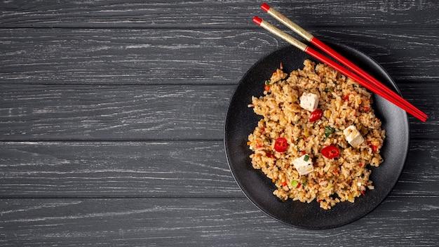 Plat lag rijst met groenten op plaat en eetstokjes met kopie ruimte