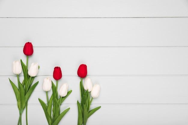 Plat lag rode en witte tulpen op tafel met kopie-ruimte