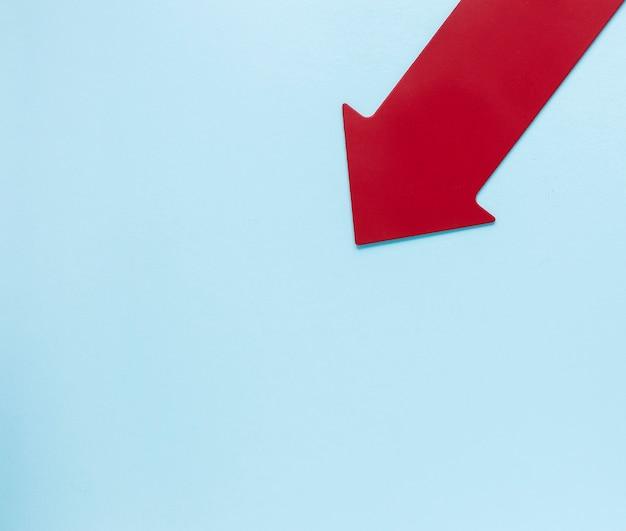 Plat lag rode pijl op blauwe achtergrond met kopie-ruimte