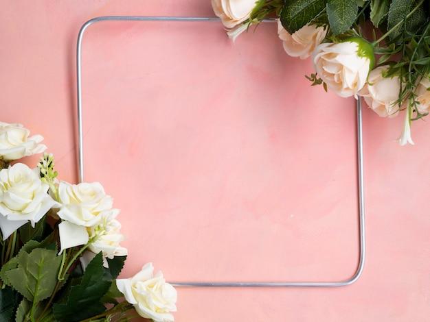 Plat lag roze achtergrond met witte rozen frame