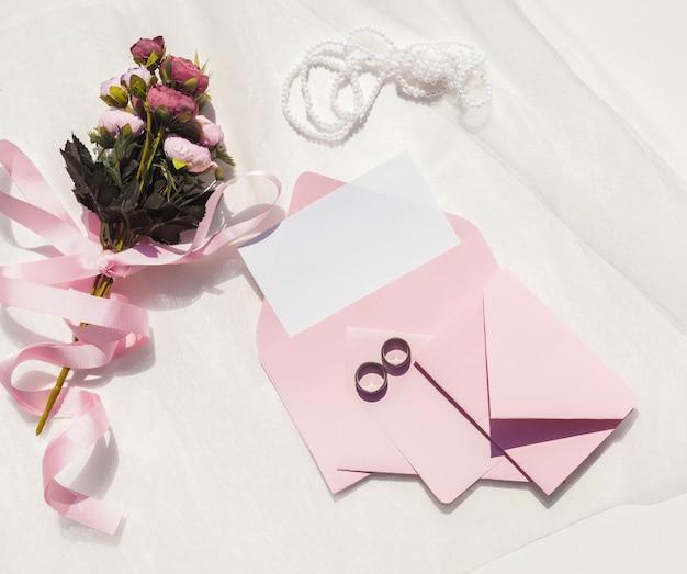 Plat lag roze bruiloft uitnodiging naast boeket rozen