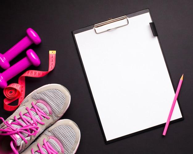 Plat lag roze sportattributen met klembord