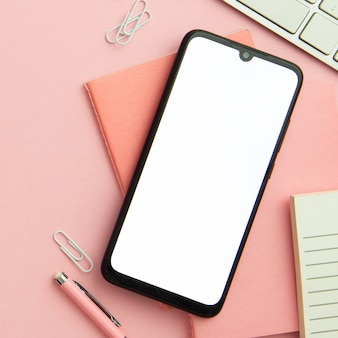 Plat lag roze werkplek regeling met lege telefoon close-up