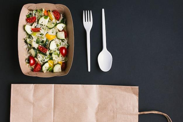 Plat lag salade en servies op zwarte achtergrond