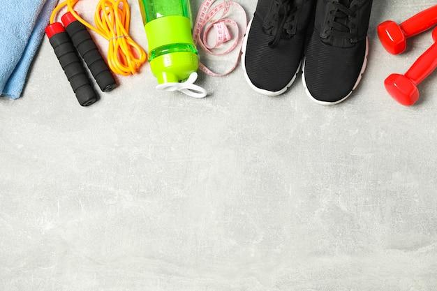 Plat lag samenstelling met accessoires voor gezonde levensstijl op grijze achtergrond