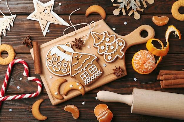 Plat lag samenstelling met bord van zelfgemaakte kerstkoekjes, mandarijn, kaneel, snoepjes, schommelstoel op houten. bovenaanzicht