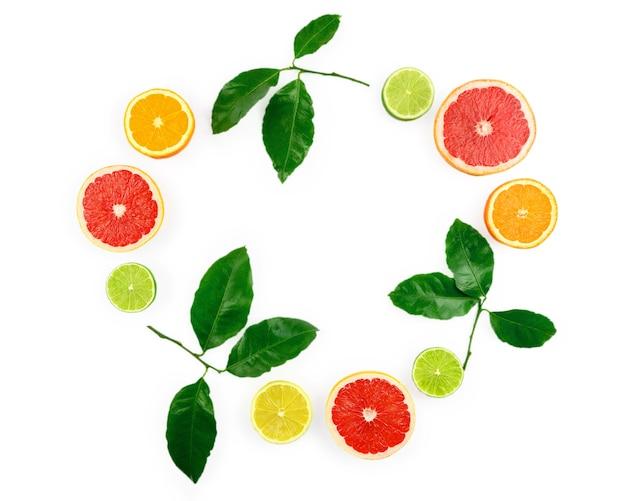 Plat lag samenstelling met citrusvruchten, bladeren en bloemen op witte achtergrond.