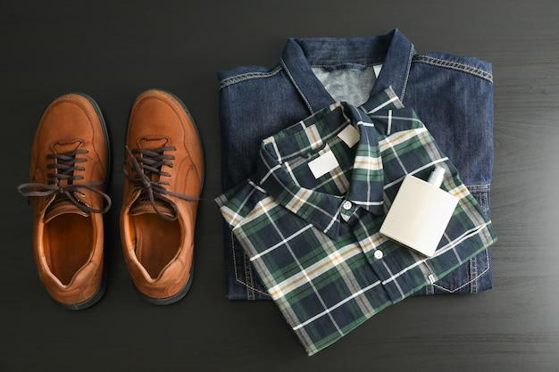 Plat lag samenstelling met denim jasje, overhemd, parfum en schoenen op zwarte tafel