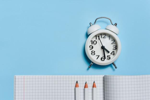 Plat lag samenstelling met een wekker, een geopend notebook en potloden op een blauwe achtergrond met een kopie ruimte.