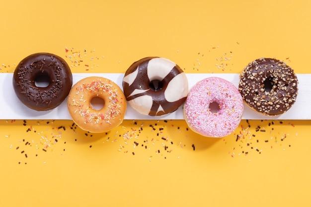 Plat lag samenstelling met gemengde donuts op gele achtergrond.