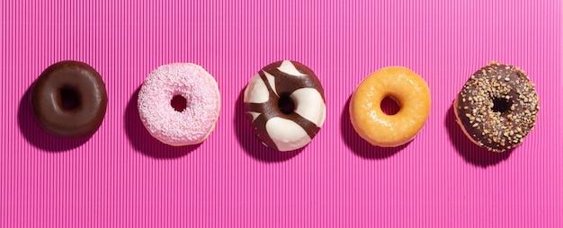Plat lag samenstelling met gemengde donuts op roze achtergrond.