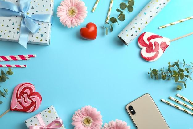 Plat lag samenstelling met gerberabloemen, geschenkdoos en snoepjes op blauw. ruimte voor tekst