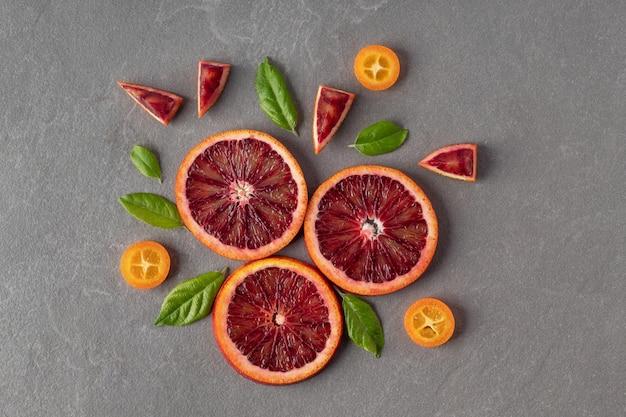 Plat lag samenstelling met gesneden bloedige sinaasappelen en kumquats op grijze achtergrond