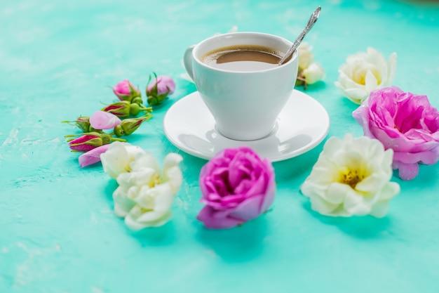 Plat lag samenstelling met knoppen bloemen en kopje koffie op een achtergrond met kleur. copy space. valentijnsdag, verjaardag, moeder of bruiloft wenskaart. gezellig en romantisch ontbijt