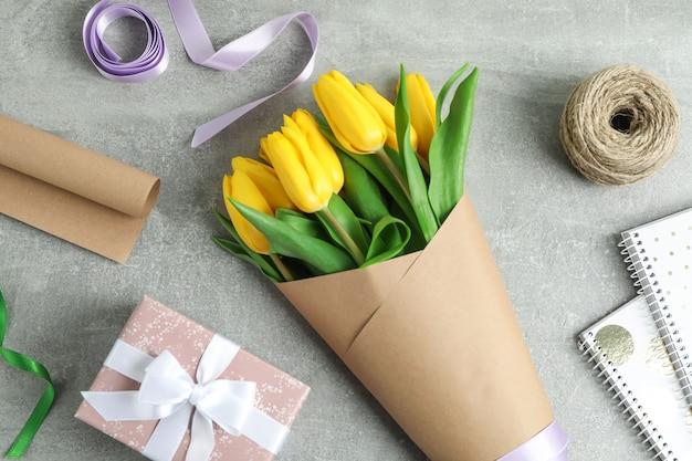 Plat lag samenstelling met prachtige bloeiende tulp bloemen en accessoires op grijs